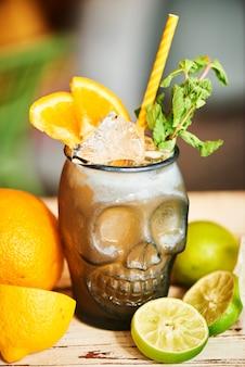 Cocktail alcolico mai tai con rum speziato fatto in casa e sciroppo di mandorle con il succo di lime in un bicchiere di vetro a forma di teschi e limone su un tavolo di legno