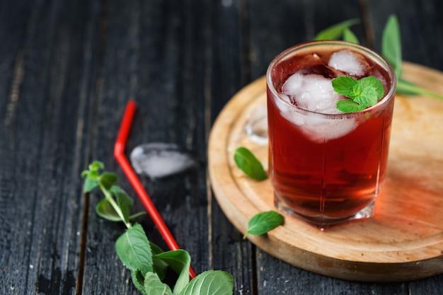 Cocktail alcolico rosso con ghiaccio e la menta in un vetro