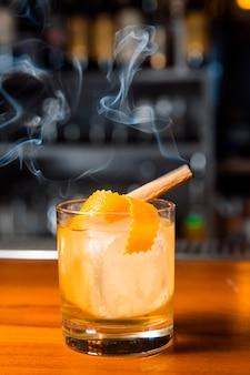 Cocktail all'arancia con cubetto di ghiaccio e scorza d'arancia.