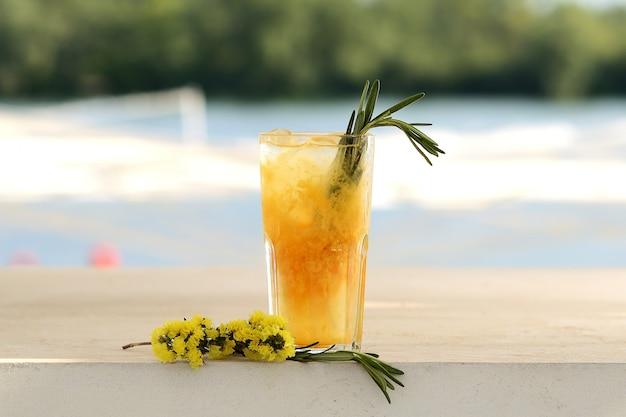 Cocktail all'arancia in un bicchiere. con decorazioni floreali