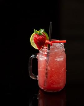 Cocktail alla fragola con ghiaccio tritato e guarnito con lime e fragola