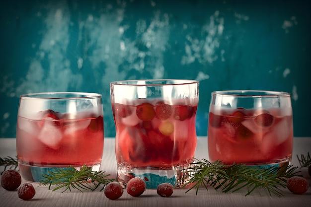 Cocktail analcolico di inverno con il mirtillo rosso e ghiaccio sulla tavola di legno