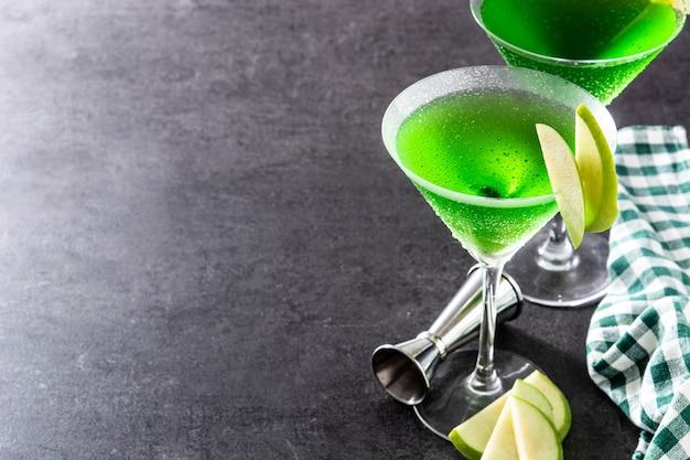Cocktail appletini verdi in vetro sulla superficie nera