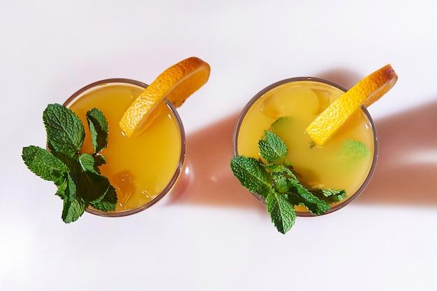 Cocktail arancione con ghiaccio decorato con rametti di menta e arancio close-up.