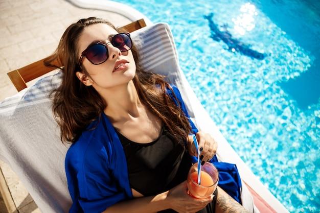 Cocktail bevente della bella donna, trovantesi sulle chaise vicino alla piscina
