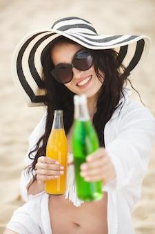 Cocktail bevente della giovane donna graziosa sulla spiaggia. ragazza attraente che offre da bere. limonata bevente della bella donna