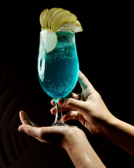 Cocktail blu con fette di mela in cima