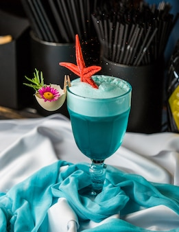 Cocktail blu della laguna con schiuma e pesce di mare.