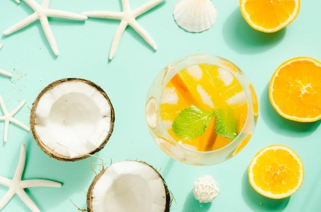 Cocktail con arancia, menta e ghiaccio vicino a noci di cocco