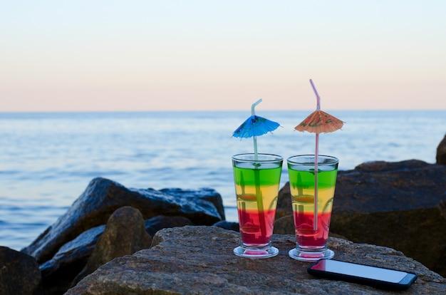 Cocktail con cannucce e smartphone sulle pietre della spiaggia