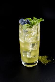 Cocktail con cubetti di ghiaccio, menta, bacche blu e whasabi sullo sfondo posteriore