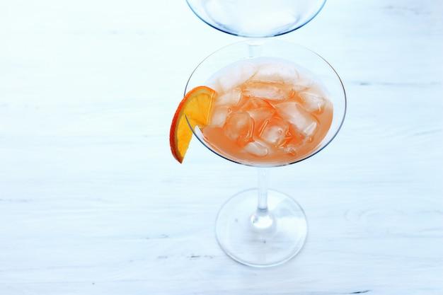 Cocktail con ghiaccio in un bicchiere sul bordo di un bicchiere di luce arancione sfondo vista dall'alto