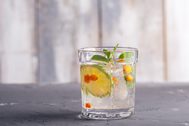 Cocktail con l'olivello spinoso e la calce su fondo grigio