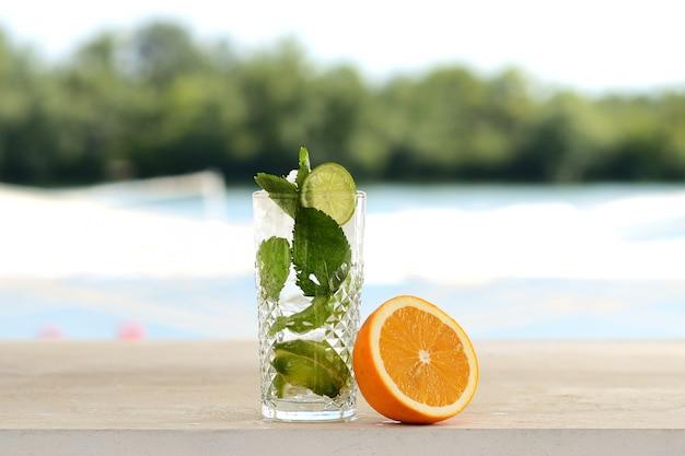 Cocktail con menta e ghiaccio in un bicchiere di vetro. con decorazioni floreali e di frutta