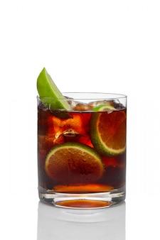 Cocktail con rum e cola con ghiaccio e lime in vetro vecchio stile isolato su bianco