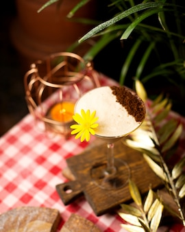 Cocktail con schiuma e cacao in polvere decorato con fiori