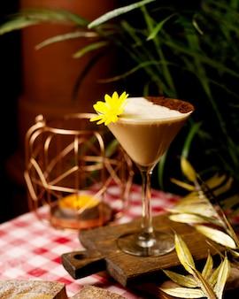 Cocktail con schiuma e polvere di cacao decorato con fiori