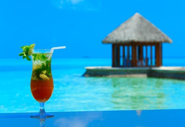 Cocktail con sfocatura spiaggia sullo sfondo