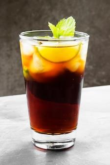 Cocktail cuba libre in un bicchiere su uno sfondo scuro