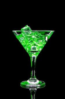 Cocktail del martini con ghiaccio e gli indicatori luminosi verdi sul nero