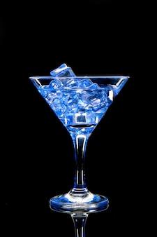 Cocktail del martini con ghiaccio e luci blu sul nero
