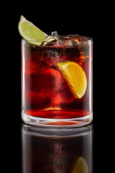 Cocktail del rum e della cola in vetro delle rocce isolato sul nero