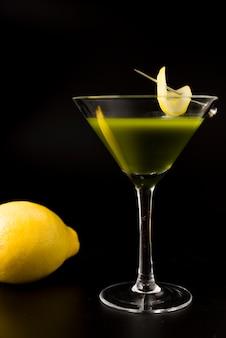 Cocktail del tè verde con il limone su fondo nero