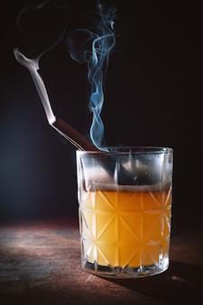 Cocktail dell'alcool con il fumo dei bastoncini di cannella