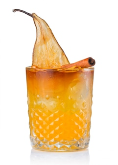 Cocktail dell'alcool della frutta con la pera e il bastone di cannella isolati