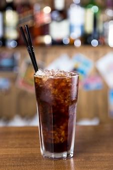 Cocktail dell'alcool sulla barra di legno con la barra