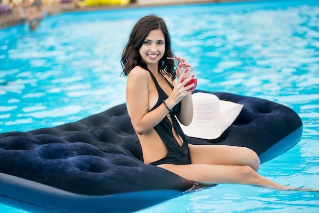 Cocktail della holding della donna che si siede sul materasso nella piscina