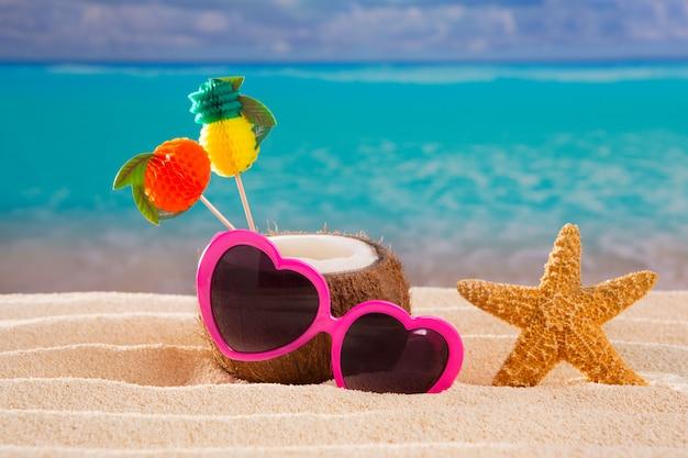 Cocktail della noce di cocco sugli occhiali da sole tropicali del cuore della spiaggia di sabbia