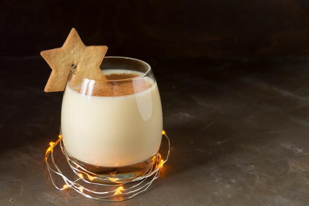 Cocktail dello zabaione e biscotti della stella su fondo nero.