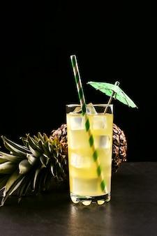 Cocktail di ananas con tubo di ghiaccio e ombrello su un frutto tropicale nero, atmosfera estiva in uno stile scuro.