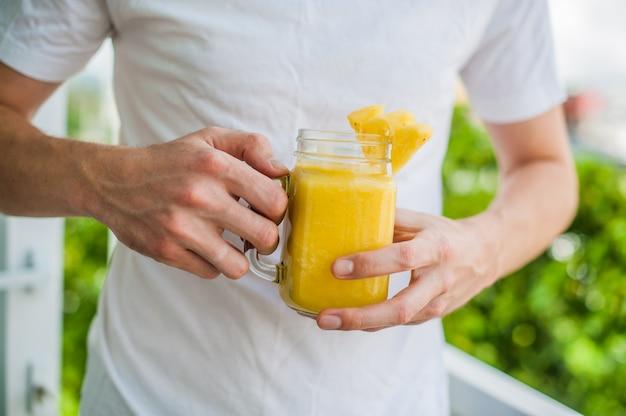 Cocktail di ananas con una fetta di uomo delle mani sulla terrazza. concetto tropicale