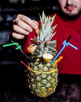 Cocktail di ananas servito in ananas con fette di mandarino e pera 1