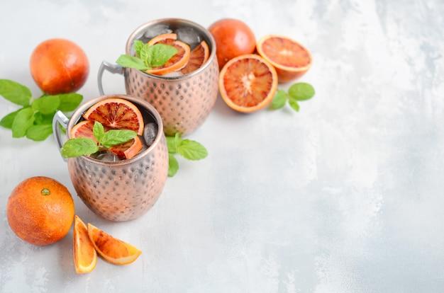 Cocktail di arancia mulo mosca mulo con foglie di menta fresca e ghiaccio in tazze di rame su uno sfondo grigio cemento.