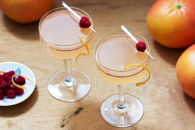 Cocktail di champagne con succo di pompelmo, guarnito con scorza e lamponi. stile rustico.