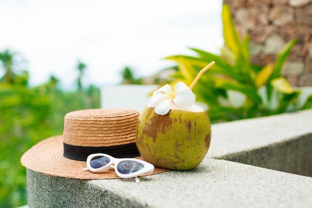 Cocktail di cocco decorato plumeria, cappello di paglia e occhiali da sole sul tavolo.