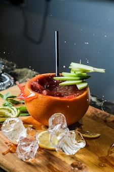 Cocktail di frutta di vista laterale in buccia d'arancia con le zeppe del limone e della mela su un tagliere