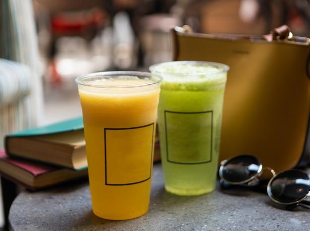 Cocktail di frutta sul tavolo con occhiali da sole, libro, borsa da donna