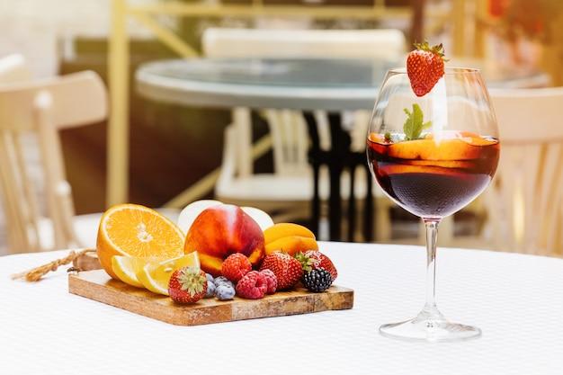 Cocktail di frutta sul tavolo di legno bianco con bacche e foglie di menta
