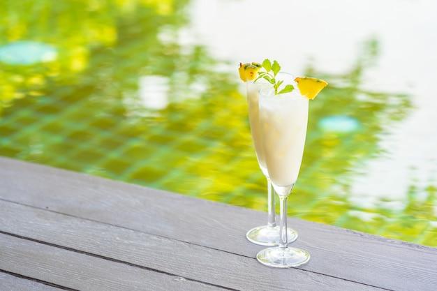 Cocktail di ghiaccio di vetro sul pavimento di legno intorno alla piscina all'aperto