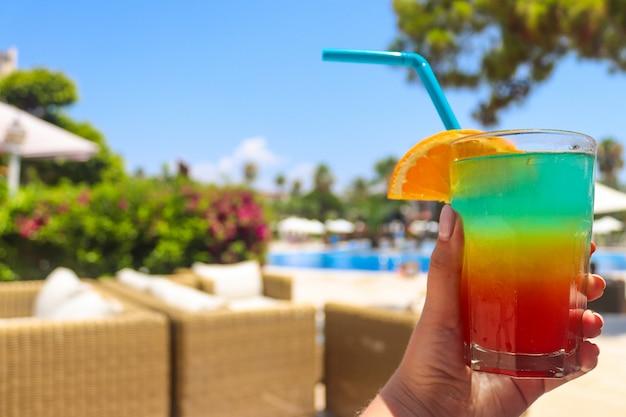 Cocktail di ghiaccio tropicale succoso colorato fresco in mano della donna vicino alla piscina.