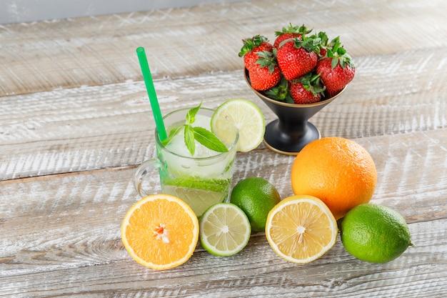 Cocktail di mojito con lime, paglia, arance, limone, fragole, menta in una tazza su superficie di legno e grigia, vista dell'angolo alto.