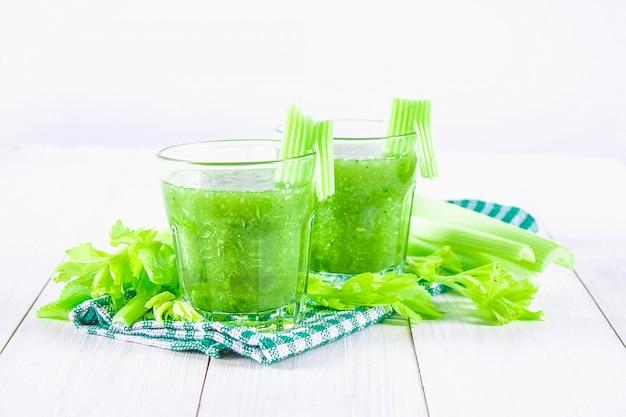 Cocktail di verdure fatto dalle foglie di sedano, stile di vita sano su un fondo di legno bianco.