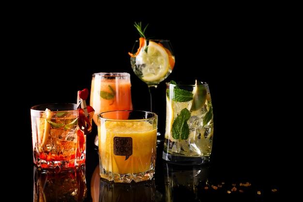 Cocktail di whisky-cola, cocktail mojito, cocktail arancione, cocktail alla fragola in bicchieri di vetro