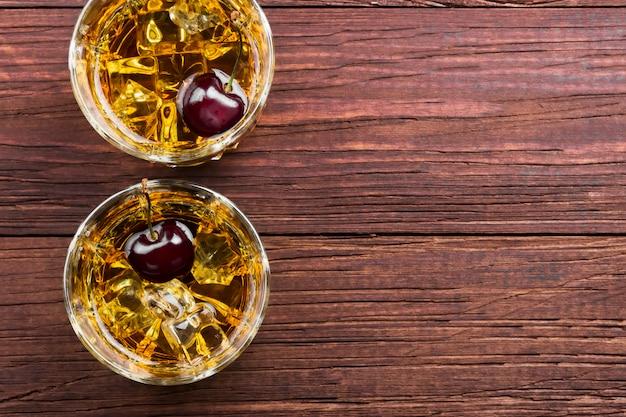 Cocktail di whisky con ciliegia in due bicchieri