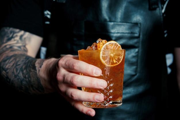 Cocktail di whisky con ghiaccio e bolle di soda, preparazione
