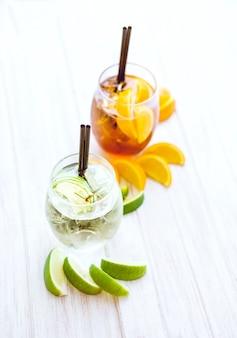 Cocktail e cubetti di ghiaccio arancio su fondo bianco.